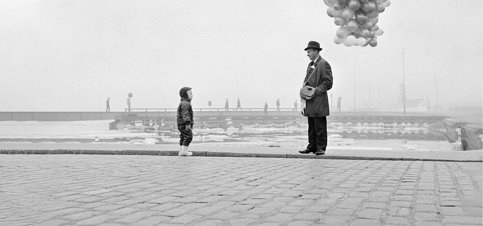 Mies, ilmapallot ja lapsi Kauppatorilla 1964